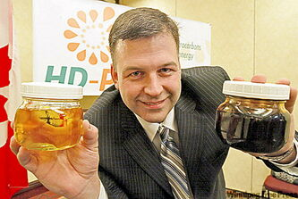Todd Habicht holds a jar of used motor oil (right) and another that has been turned into diesel fuel.