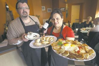 Jose Strurym, left, with torta mil hojas dessert and Tempranillo wine and his restaurant assistant Milagros Rodrigues with empanadas and Milanesa Especial.