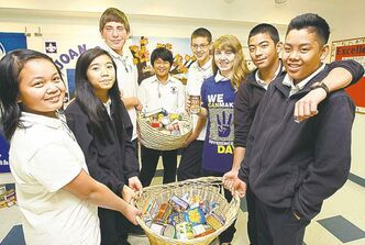 Holy Cross School students Angelique Pangilinan (from left), Mary Masangkay, Gabriele Cayabyab, Ronald Zacharias, Nicole Drouin, Bryner Danan and Patrick Susi hold food collected for the needy. Students at the school run various charity fundraisers inspired by We Day.
