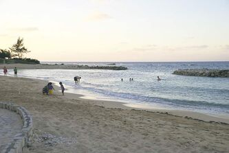 Families enjoy Half Moon Beach before nightfall.