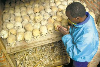 A Rwandan survivor of the 1994 genocide prays over the bones of genocide victims at a mass grave in Nyamata, Rwanda, on April 6, 2004, the 10th anniversary of the atrocity.