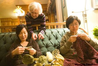 Edna Peters (centre) checks out Heiran Jun's (left) and Soyoun Han's knitting progress at Peters' home.