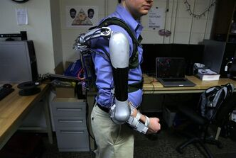 In this Friday, Dec. 6, 2013 photo, Nick McGill wears the Titan Arm as he poses at the University of Pennsylvania in Philadelphia. The robotic device invented by four University of Pennsylvania engineering students can help its wearer carry an additional 40 pounds. The prize-winning prototype builds on existing research in the field of exoskeletons, an area that experts say will grow as the population ages. Students say some current exoskeleton models can cost $100,000. They created the award-winning Titan Arm for less than $2,000. (AP Photo/Jacqueline Larma)