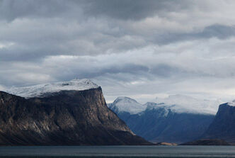 Shaft of sunlight strikes mountains in Pangnirtung Fiord, Nunavut.