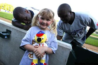 Ashley Kuhlman, 5, gets her T-shirt signed by Goldeyes Dee Brown, left, and Vince Harrison Wednesday night. The Fish kick off their 17th season tonight at Canwest Park against the Lake County Fielders