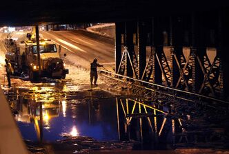 Crews work to drain the flooded McPhillips Street underpass after a Monday morning water main break.