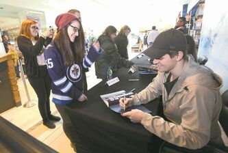 Jets forward Mark Scheifele, who contributed a recipe for a banana-blueberry smoothy, signs a copy of Our Jets at Home for Megan Wray, a big fan of No. 55, at St. Vital Centre on Saturday.