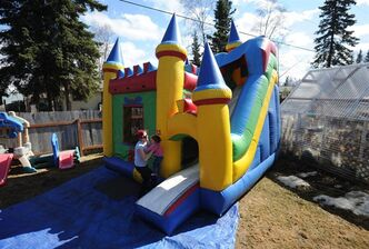 Michelle Appel, owner of Fun For Alaska, watches as her pre-school children and others play in a Castle combo bounce house in her backyard on Tuesday, April 29, 2014, in Anchorage, Alaska. (AP Photo/The Anchorage Daily News, Bill Roth) LOCAL TV OUT (KTUU-TV, KTVA-TV) LOCAL PRINT OUT (THE ANCHORAGE PRESS, THE ALASKA DISPATCH) )