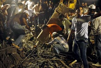 Rescue workers search for survivors after a building filled with as many as 150 people collapsed in Mumbai Thursday.