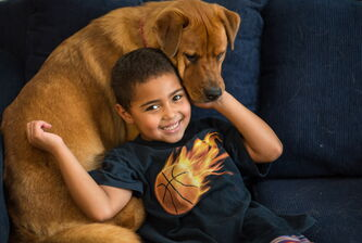 "Tyler, 6, born a girl and known until 2 years ago as Kathryn, poses for a portrait with his dog, ""Princess,"" at his Washington-area home. His parents allowed him to present himself as a boy when he was 4, after he was diagnosed with gender identity disorder. They say they have no second thoughts about their decision."