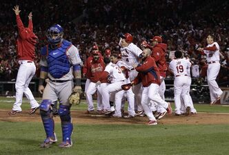 Texas Rangers catcher Mike Napoli walks away as the St. Louis Cardinals celebrate after David Freese hit a walk-off home run during the 11th inning of Game 6 of baseball's World Series Thursday, Oct. 27, 2011, in St. Louis. (AP Photo/Matt Slocum)
