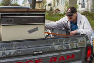 Pat Hilton secures a dishwasher to the truck after finding it on the curb along Arlington Street Saturday morning. May 12-13 is giveaway weekend, when residents put free items on their curbs for the picking.