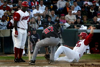 Goldeye #30 Kevin West is tagged at home by RedHawks pitcher Nick Fellman, while Goldeye batter Dee Brown watches in a scoreless fifth inning Tuesday at the ballpark in Winnipeg.