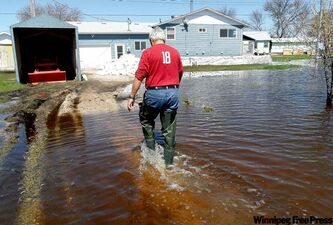 Fred Pisclevich on his flooded driveway at his home in Twin Lakes Beach.