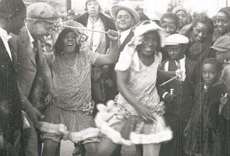 "This still frame from a film strip provided by Story Sloan Gallery shows women dressed as ""baby dolls"" dancing on a New Orleans street at Mardi Gras in 1931. The first known group of women to strut and dance in short 'baby doll' dresses was a group of African-American prostitutes who wanted to outdo another group in 1912, but the style soon spread to respectable black neighborhoods and is seeing a modern revival."