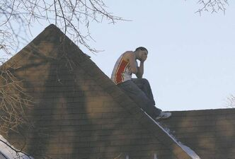 Joe Bryksa / Winnipeg Free PressTrying to evade police, an auto-theft suspect sits on a roof in the 400 block of Furby Street Thursday morning. An aerial ladder was used to get him down.