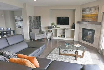 An angled rear wall in the family room features a gas fireplace set in grey tile with a dark maple mantel.