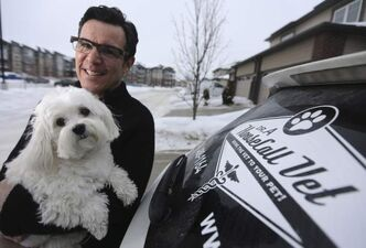 Adelman, and his dog, Maggie, next to his house-call veterinary service vehicle.