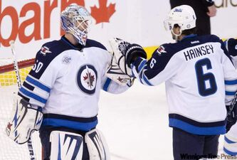 The Winnipeg Jets' Ron Hainsey congratulates goalie Chris Mason on the shutout as the Jets defeated the Senators 2-0 in Ottawa, on Monday.
