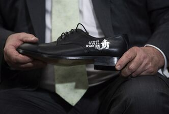 Finance Minister Jim Flaherty gets ready to put on his annual pre-budget shoes at the Roots Leather Factory in Toronto on Wednesday, March 20, 2013. THE CANADIAN PRESS/Nathan Denette