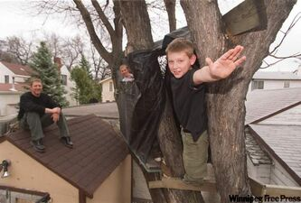 Slater with his now-grown boys, Riley (peeking out at left) and Jeff, in a tree house he built for them.