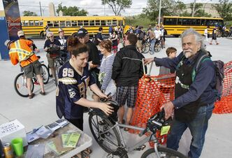 Bike valet Bill Newman (right) takes care of fans bikes as Winnipeggers arrive at Investors Group Field Thursday night.