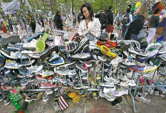 Notes are written on running shoes at a memorial near the finish line of the Boston Marathon, one month after the bombing.