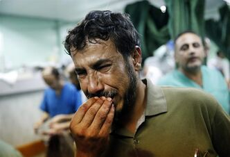 A Palestinian man cries after bringing a child, wounded in an Israeli strike on a compound housing a U.N. school in Beit Hanoun, in the northern Gaza Strip, to the emergency room room of the Kamal Adwan hospital in Beit Lahiya, Thursday, July 24, 2014. Israeli tank shells hit the compound, killing more than a dozen people and wounding dozens more who were seeking shelter from fierce clashes on the streets outside. Gaza health official Ashraf al-Kidra says the dead and injured in the school compound were among hundreds of people seeking shelter from heavy fighting in the area. (AP Photo/Lefteris Pitarakis)