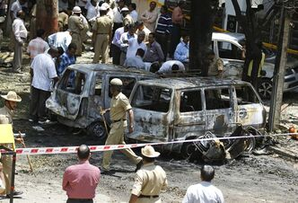 Policemen and officials inspect the site of an explosion at a residential neighborhood near the office of India's main opposition Bharatiya Janata Party in Bangalore, India, Wednesday, April 17, 2013. A powerful bomb exploded Wednesday near the office of the political party, injuring at least 16 people, police said. (AP Photo/Aijaz Rahi)