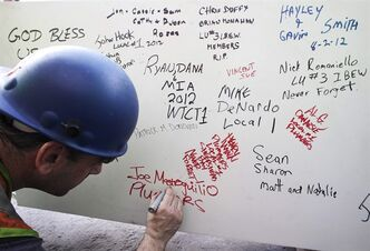 FILE- In this Aug. 2, 2012 file photo, a construction worker signs a ceremonial steel beam at One World Trade Center in New York. The beam was signed by President Barack Obama with the notes: