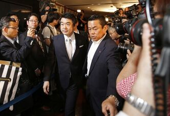 Osaka Mayor Toru Hashimoto, center left, arrives at the Foreign Correspondents' Club of Japan in Tokyo for a news conference Monday, May 27, 2013. The outspoken Japanese politician apologized Monday for saying U.S. troops should patronize adult entertainment businesses as a way to reduce rapes, but defended another controversial remark about Japan's use of sex slaves during World War II. (AP Photo/Shizuo Kambayashi)