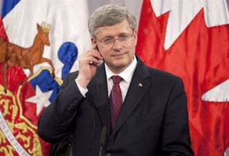 Canadian Prime Minister Stephen Harper listens to his translation aid as Chilean President Sebastian Pinera makes opening remarks during a joint news conference at the Presidential palace in Santiago, Chile, Monday April 16, 2012. THE CANADIAN PRESS/Adrian Wyld