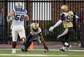 Winnipeg Blue Bombers defensive back Desia Dunn scores a touchdown on a pass interception in front of teammate Jason Vega and Montreal Alouettes centre Luc Brodeur-Jourdain during second quarter CFL football action Friday, July 11, 2014 in Montreal.