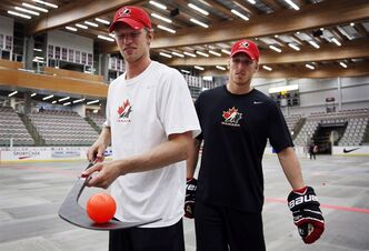 Eric Staal, left, from Thunder Bay, Ont., balance a ball on his stick as his brother Marc Staal, from Thunder Bay, Ont., looks on in Calgary, Alta., Tuesday, Aug. 27, 2013.THE CANADIAN PRESS/Jeff McIntosh
