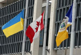 From left: the Ukrainian flag, Canadian flag and City of Winnipeg flag all stand at half-mast  in front of Winnipeg City Hall Wednesday.