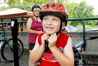 Alex Dynkavitch, 6, and mother, Carol, head off for a bike ride wearing their helmets.