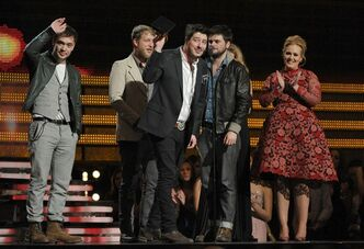 "Mumford & Sons, from left, Ben Lovett, Ted Dwayne, Marcus Mumford and Country Winston Marshall accept the award for album of the year for ""Babel"" at the 55th annual Grammy Awards on Sunday, Feb. 10, 2013, in Los Angeles. Presenter Adele, right, claps. (Photo by John Shearer/Invision/AP)"