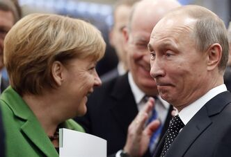 Russian President Vladimir Putin and German Chancellor Angela Merkel chat during the opening of the Hannover Fair in Hannover, Germany, Monday, April 8, 2013. (AP Photo/Frank Augstein)
