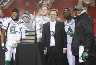 Saskatchewan's Geroy Simon (left to right), Weston Dressler, Craig Butler, GM Brendan Taman, Darian Durant, and head coach Corey Chamblin pose with the West final trophy, earning a trip to the Grey Cup.