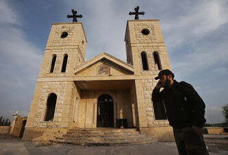 A commander of the Ghurabaa al-Sham  brigade  earlier this year in front of a church shelled by mortars, at Judeida, one  of the first  Christian  villages to be taken by the rebel Syrian army.