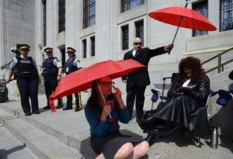 Dominatrix Terri-Jean Bedford (right) sits on the front steps to the Supreme Court of Canada in Ottawa on Thursday, June 13, 2013. The SCOC is hearing arguments on the constitutionality of Canada's prostitution laws. THE CANADIAN PRESS/Sean Kilpatrick