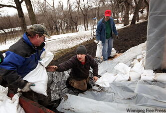 Brian Witthoeft, left to right, Joel Witthoeft and Neil Dyer prepare Brian's Moorhead home for flooding as the Red River rises on Monday.