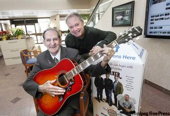 Winnipegger Philip J. Cheverie, with head angel Kevin Rollason, holds the guitar autographed by Doc Walker he won in the Pennies from Heaven contest.