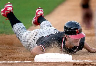 RedHawks' Zach Penprase is kept close to the base after a fourth-inning throw by  Goldeyes pitcher Louis Villarreal.