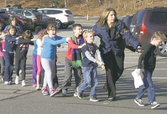 Connecticut State Police lead a line of children from the Sandy Hook Elementary School in Newtown, Conn.