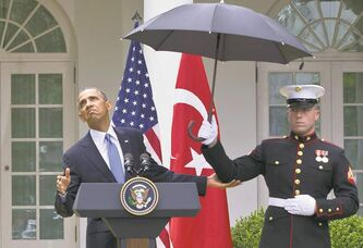 U.S. President Barack Obama leans out from under an umbrella held by a marine on Thursday.