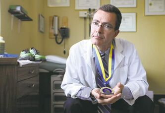 Dr. Tim McCarthy with his Boston Marathon medal. He returned to a life punctuated by wide eyes and worried messages. Dozens of patients called hoping their rheumatologist was OK.