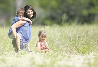 Adrienne with Noah and Hannah in a field of wild flowers behind their farm.