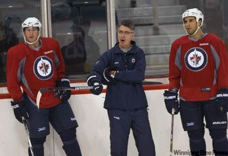 Winnipeg Jets players Shawn Weller (left) and Bryan Little listen as head coach Claude Noel gives instructions at training camp at the MTS Centre on Sunday afternoon.