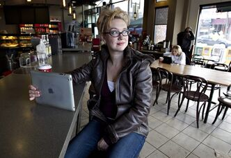 Tanis Miller poses for a photo as she watches a movie on her iPad at a coffee shop in Edmonton on Friday, November 26, 2012. THE CANADIAN PRESS/Jason Franson